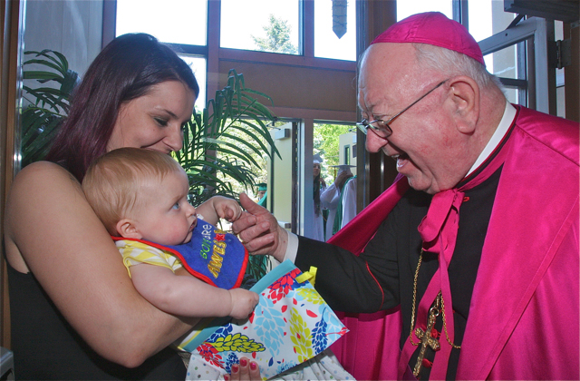 Bishop William Murphy gets friendly with Alyson Touhey of Pennsylvania and her 10-month-old son Killian before the graduation ceremony. (Credit: Barbaraellen Koch)