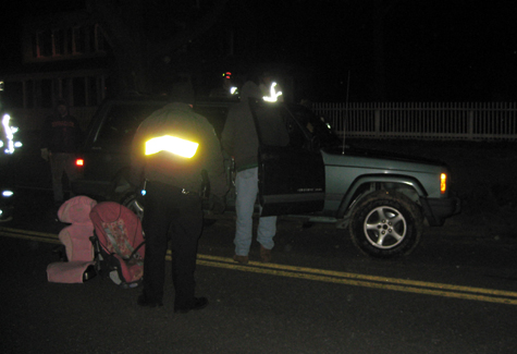 MICHAEL WHITE PHOTO | Police and firefighters after righting a Jeep Cherokee that had flipped onto its side in the westbound lanes of Sound Avenue near Martha Clara Vineyards.