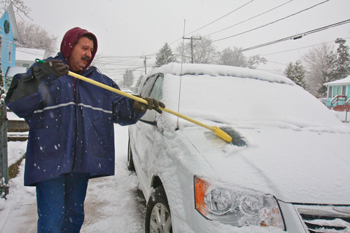 BARBARAELLEN KOCH PHOTO | Town worker Juan Ayala had off on Monday but came out to clean off his nephew's car at his Hamilton Avenue. School district plows heads down Marcy Avenue.