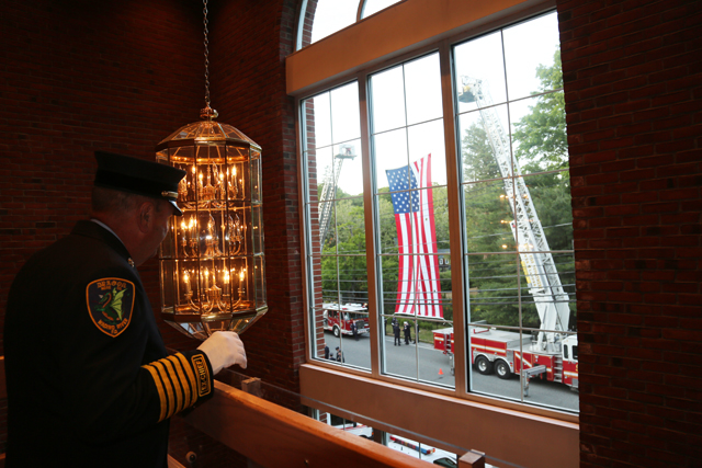 A Wading River fireman looks out the window to the American flag. (Credit: Nicole Smith)