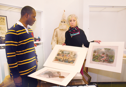 BARBARAELLEN KOCH PHOTOCurator David Byer-Tyre and SCHS executive director Kathy Curran holding  Currier and Ives 'Dark Town' series prints.