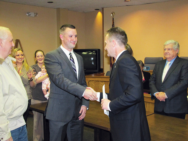 Riverhead police officer Chris Burns is congratulated by Supervisor Sean Walter. (Credit: Tim Gannon)