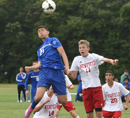 Riverhead's Jonathan Perez rises to head a corner kick while being challenged by Newfield's Connor Timmonds (10). (Credit: Garret Meade)