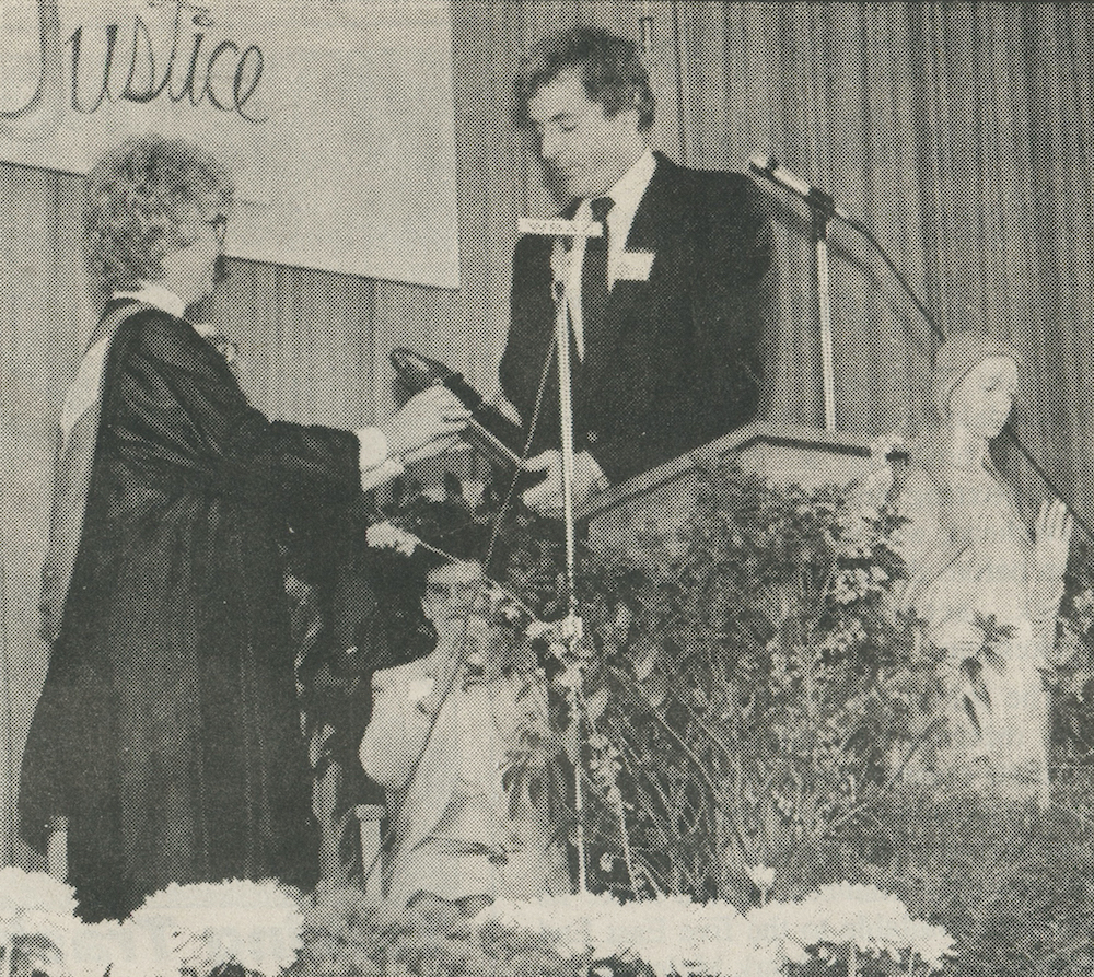 In March 1990, Mercy High School principal Sister Elaine Hanson accepted the school's 1989 state School of Excellence award from Department of Education representative Herbert Stupp in a ceremony at the school.
