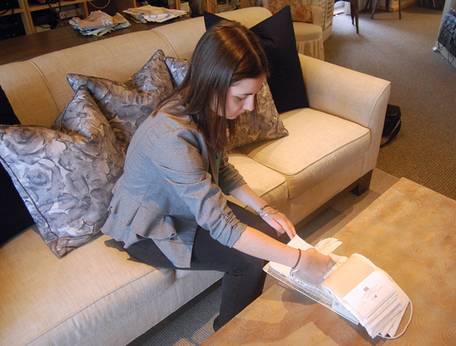 RACHEL YOUNG PHOTO Emily Demarest, an interior designer at Wallace Home Design in Southold, goes through fabric swatches. She said warm colors, like cream and gold, are popular right now. (Credit: Rachel Young)